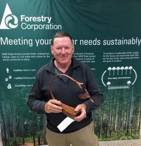 Winner holds hummingbird carving